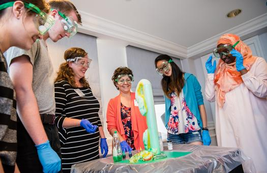 Society Advocates (center) show students an elephant toothpaste experiment at the Advocate Training Institute in 2017.
