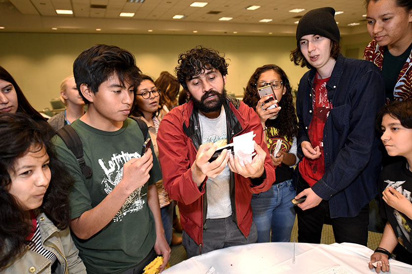 Manu Prakash shows students how to make and use his foldscope microscope at Education Outreach Day during Intel ISEF 2017.