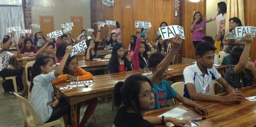 Students raise signs during the research quiz competition portion of the workshop.