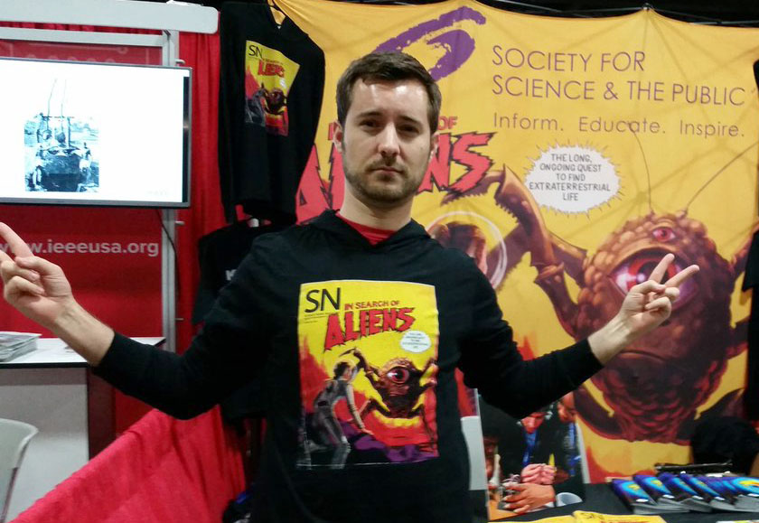 A member of the public wears the Society's sweatshirt with a cover of <em>Science News.</em>