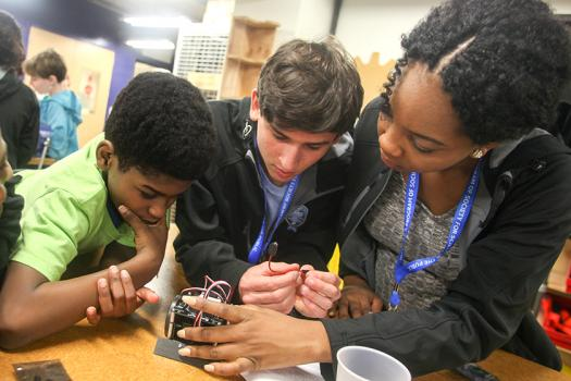 Thomas Colburn (middle) and another Intel STS 2016 finalist help students in Washington, D.C. create circuits.