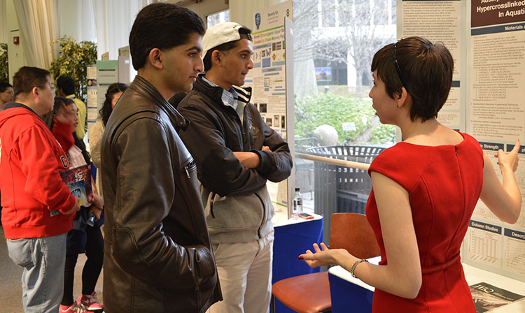 Maria Elena Grimmett explains her project to members of the public.