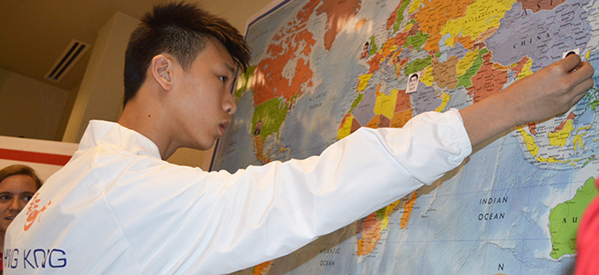 A delegate from Hong Kong places his photo on a world map.