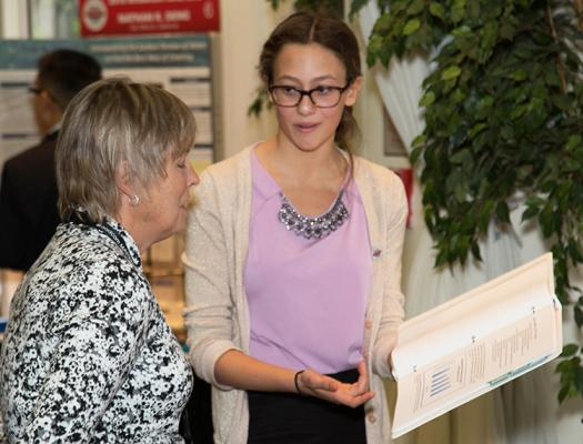 Aria describes her research with a judge at the 2016 Broadcom MASTERS Project Showcase.