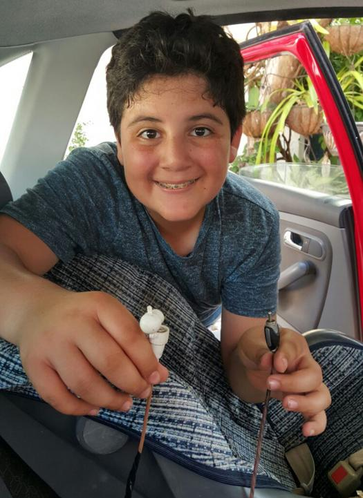 Joaquin holds up his car seat alarm system inside a car.