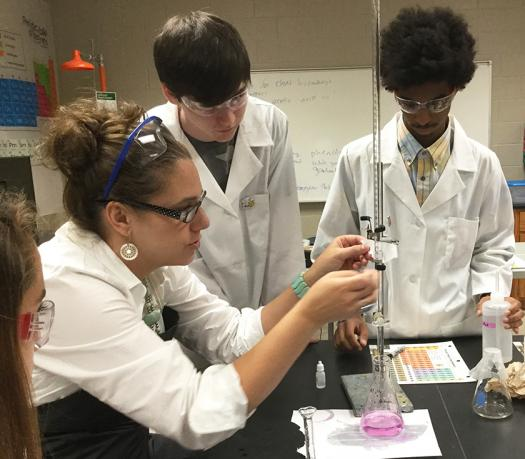 Elizabeth helps her students with a lab experiment.