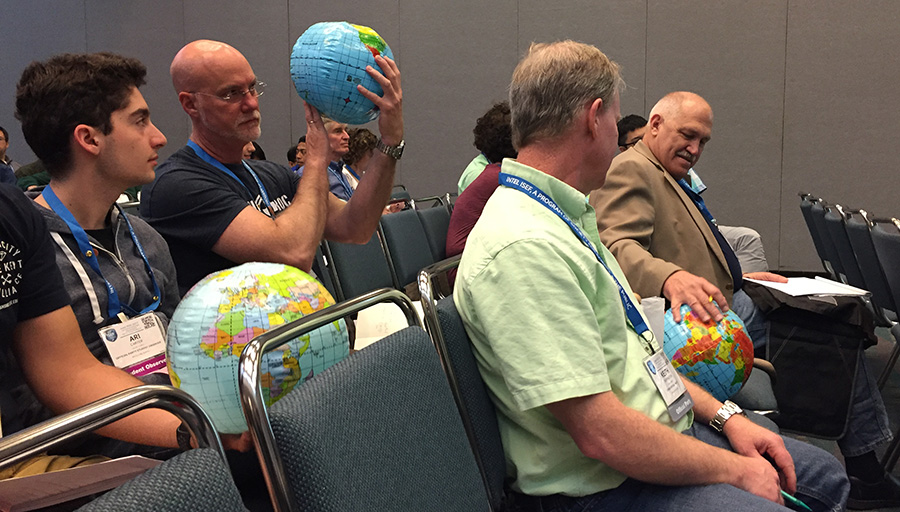 Symposia audience members inspect inflatable globes to learn about climate change modeling.