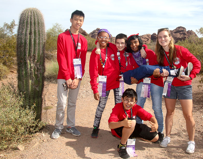A group of delegates surround a saguaro cactus in Arizona.