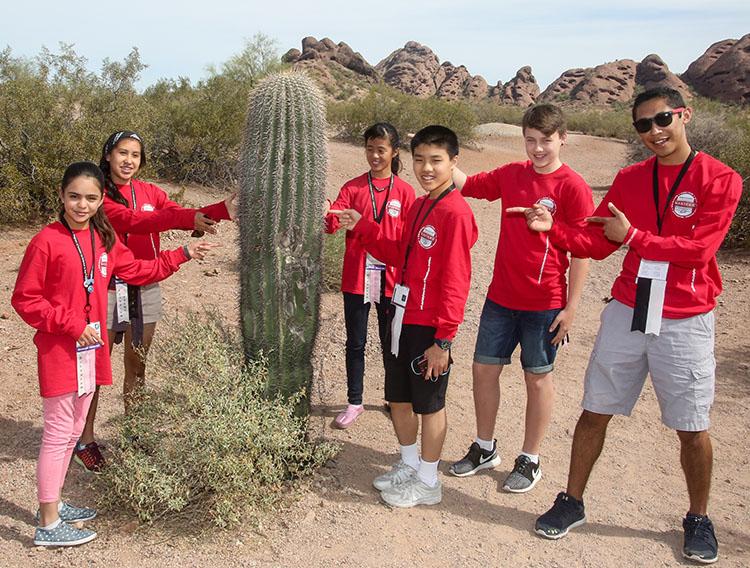 A group of delegates surround a saguaro cactus on their tour of the Desert Botanical Garden.