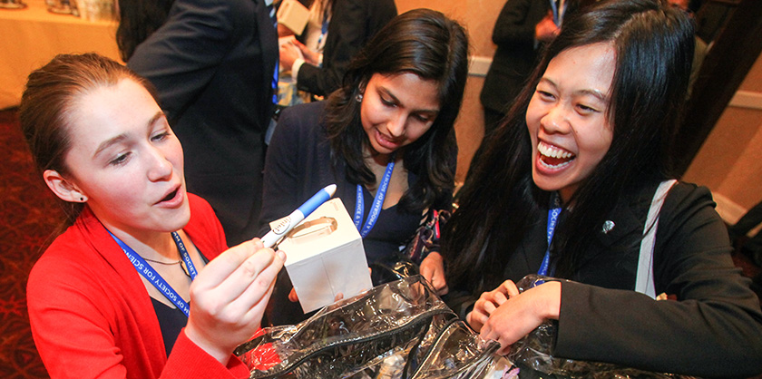 First-place winner Paige Brown, and finalists Meena Jagadeesan and Catherine Jessica Yihui Li open their presents after the Intel Innovation dinner.