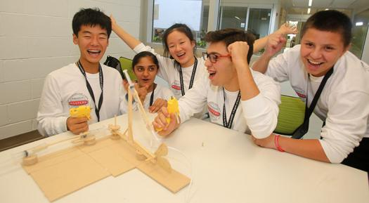 The white team celebrates after making a robotic blue crab arm.