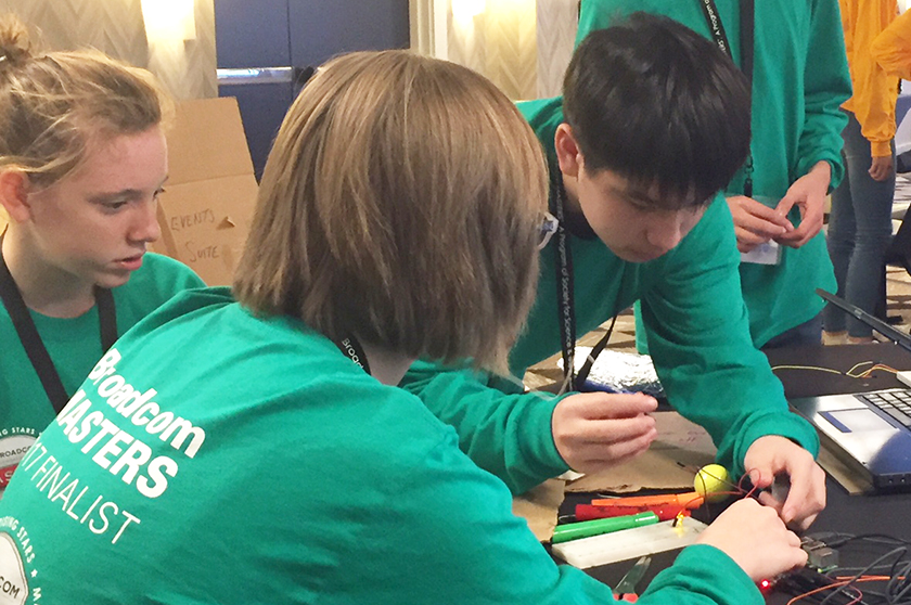 Members of the green team attach wires to their raspberry pi.
