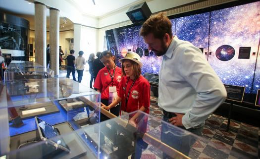 Pei-Yun Chang, from Taiwan, and Giancarlo Villaverde, from Puerto Rico, learn about the progress of telescopes alongside David Garrett, a Distinguished Engineer at Broadcom at the Griffith Observatory.