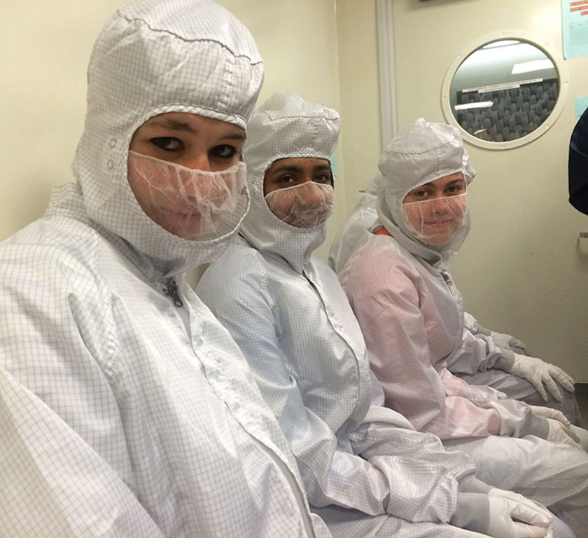 Camille, Tiasha, and Nicky wore bunny suits in a clean room during a tour at Caltech.