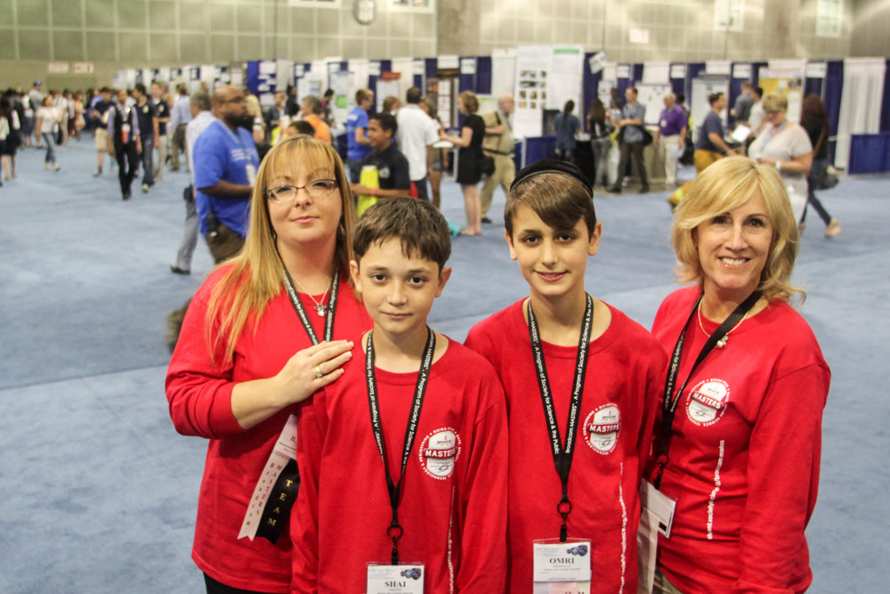 Israeli delegates Shai Grizek and Omri Mishaly with Paula Golden and Ilanit Drori from Broadcom in the Intel ISEF finalist hall.