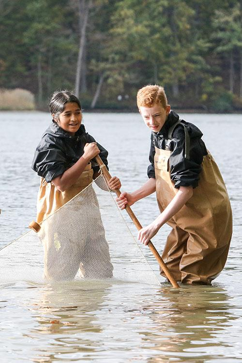 Ananya Ganesh and Brendan Crotty waded into the Chesapeake Bay to caught wildlife in large nets, called seining. ~~ Photo courtesy of Society for Science & the Public/Linda Doane.