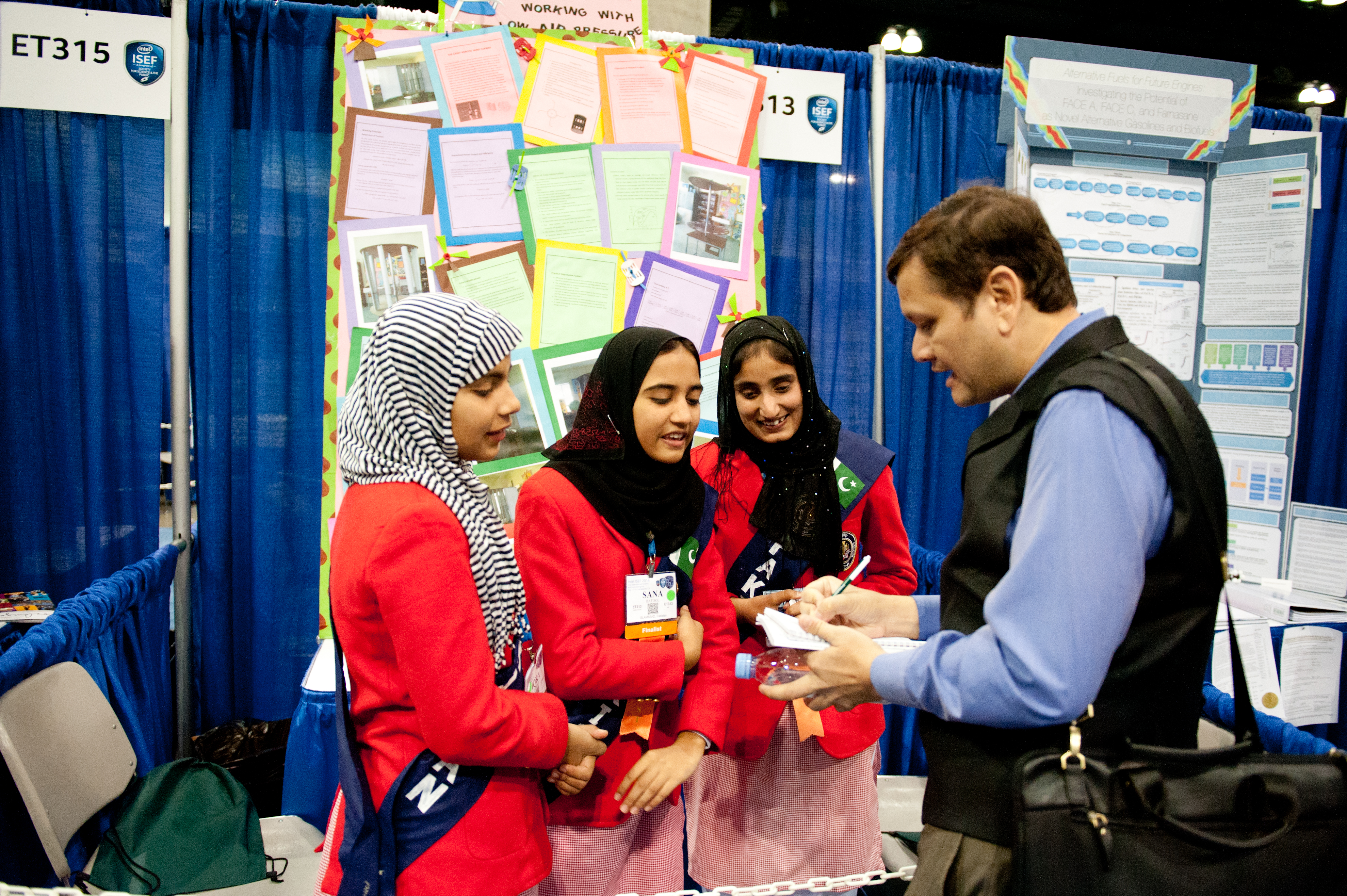 A judge speaks to participants at Intel ISEF 2014.