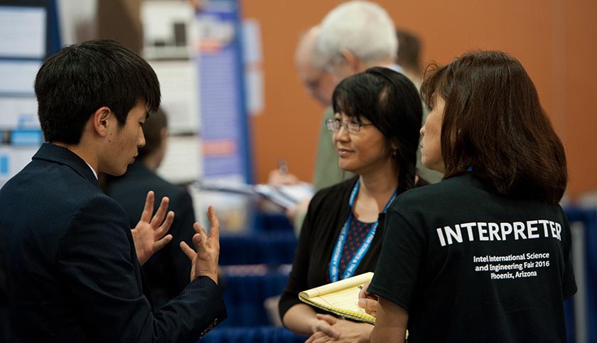 An interpreter helps a 2016 Intel ISEF finalist explain his project to a judge.