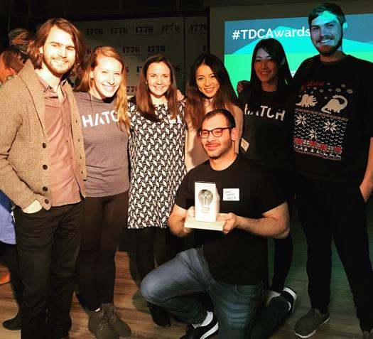 The Hatch Apps team hold up an award.