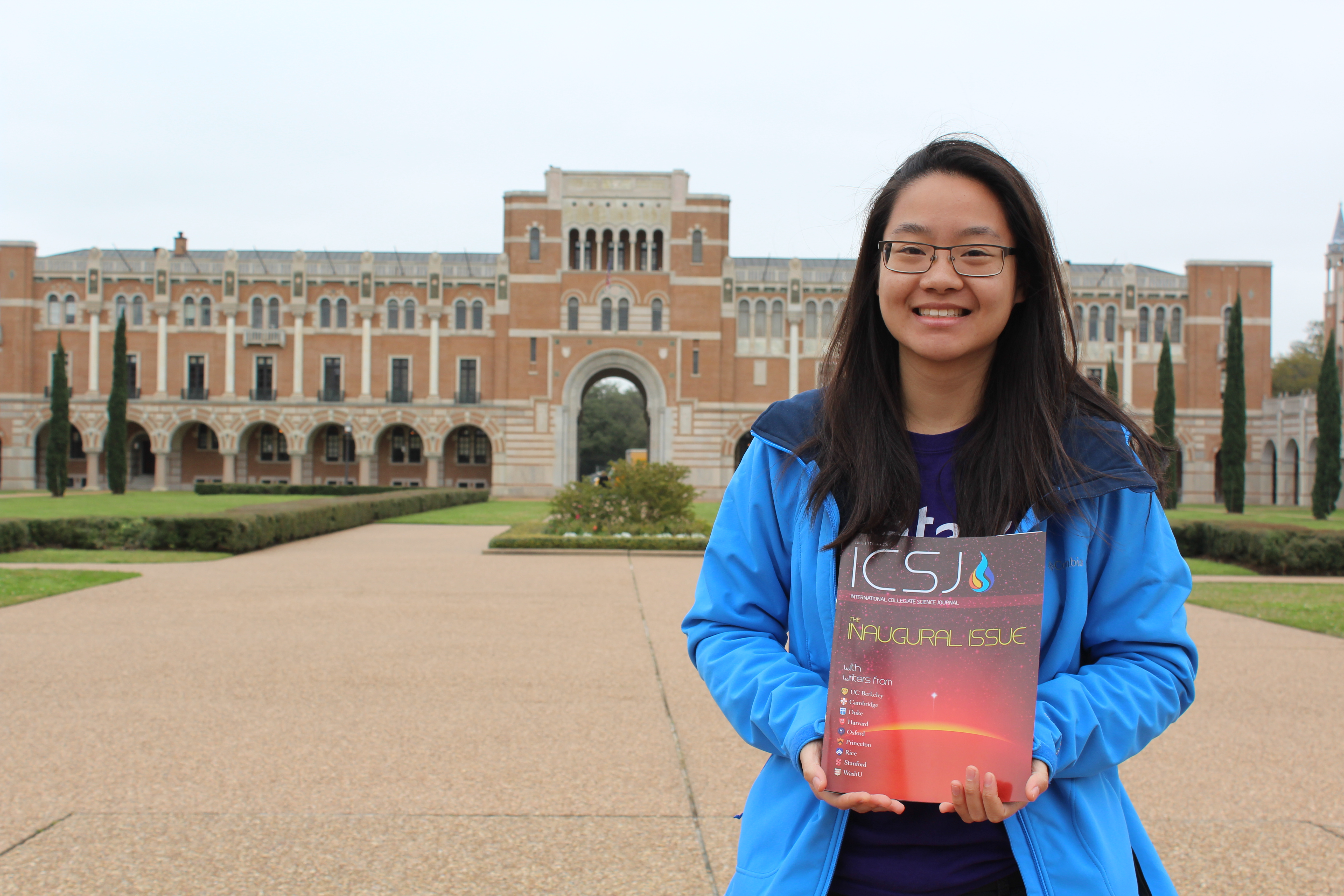 Julia Zhao holds a copy of the International Collegiate Science Journal  on the grounds of  Rice University's campus.