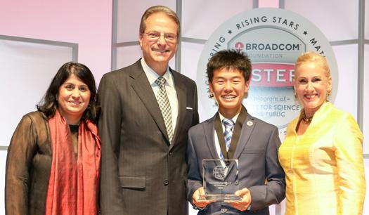 Kaien holds up his award with President & CEO of the Society Maya Ajmera (left), Co-founder of the Broadcom Foundation Henry Samueli, and President of the Broadcom Foundation Paula Golden.