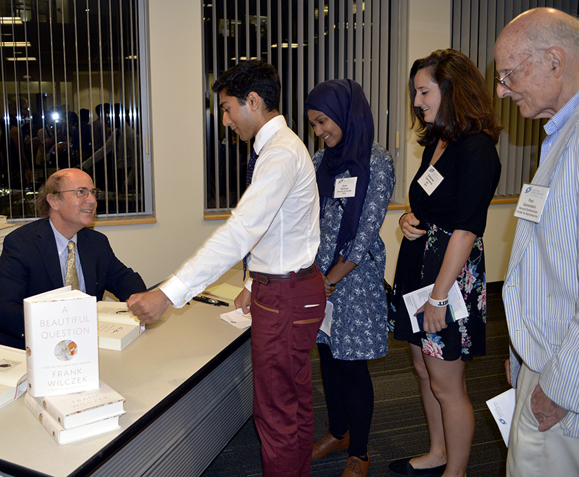 STS alumni Shaun Datta, Zarin Rahman, and Kathy Camenzind and Society guest Dr. Paul Gorenstein (far right) gather to have Frank Wilczek sign copies of his new book.