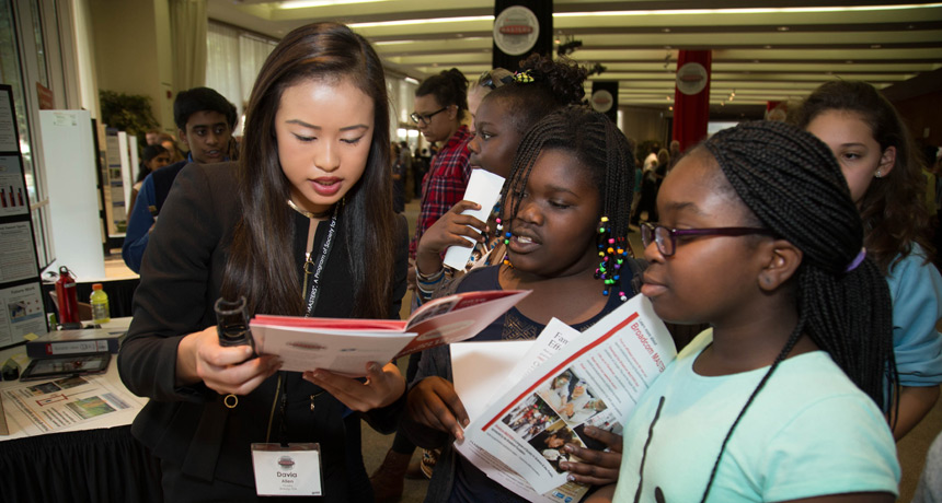 Davia Allen (left) explains her project to students at the Broadcom MASTERS public presentation of projects in Washington, D.C.