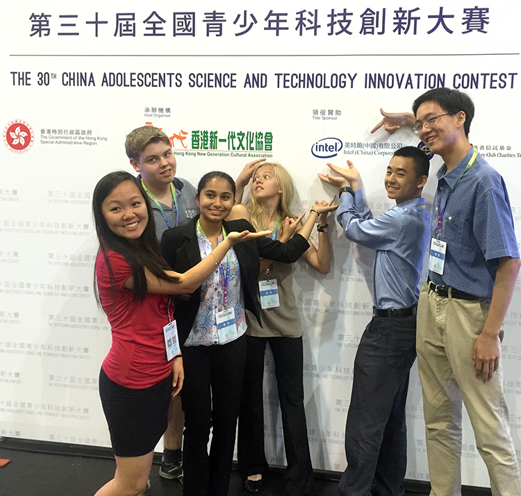 Intel ISEF finalists stand in front of a China Adolescent Science & Technology Innovation Contest Intel sign.