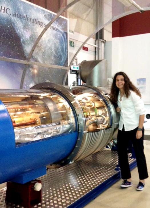Francisca stands next to a model of LHC tubes.