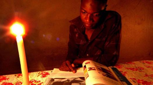 Students often have to read by candlelight to complete their homework due to a shortage of electricity in Zimbabwe.