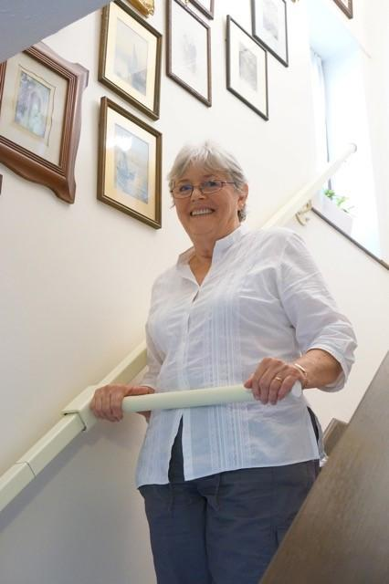 A woman uses the StairSteady, invented by Ruth Amos.