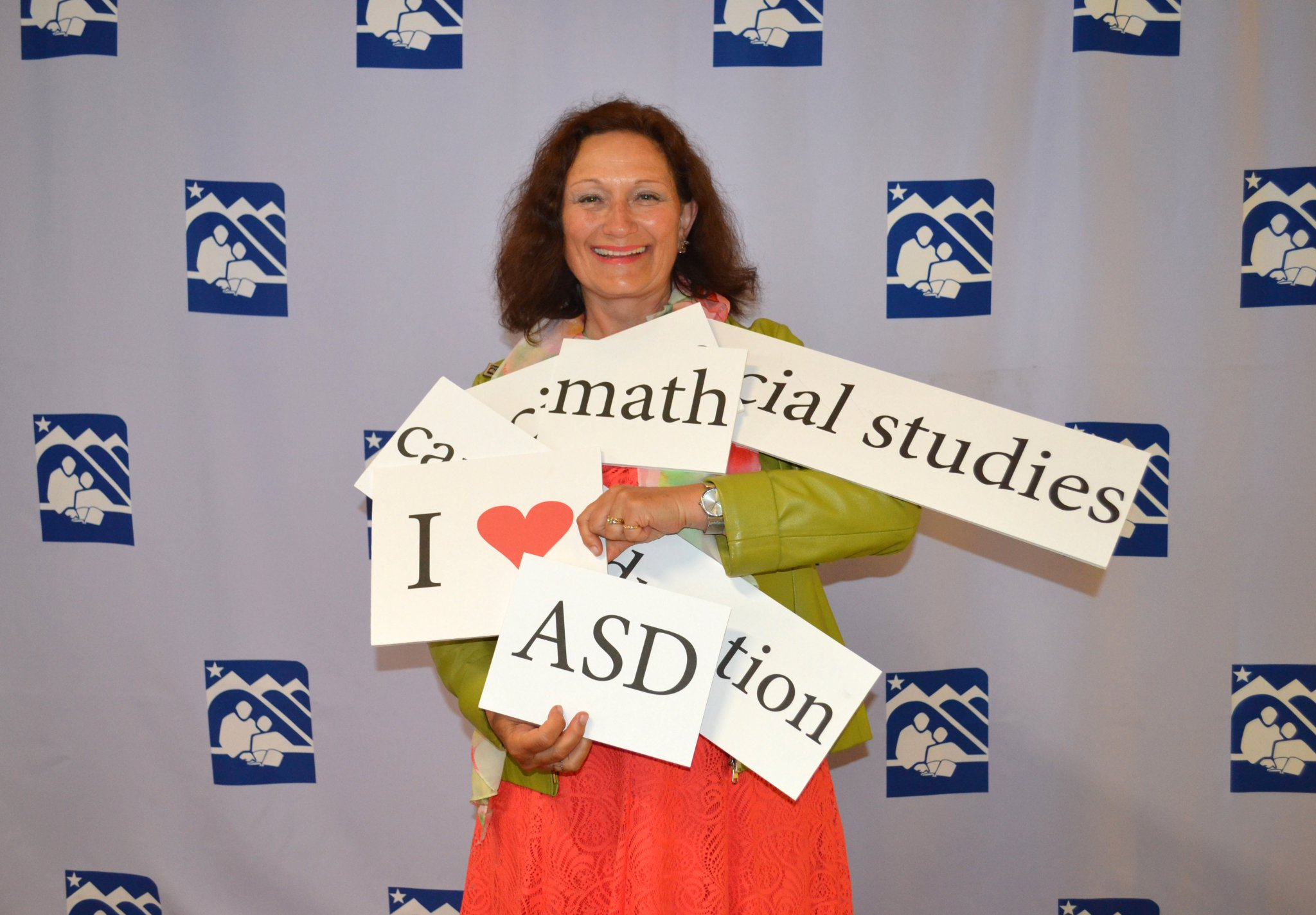 Tam holds up signs celebrating the Anchorage School District.