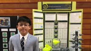 Jordan in front of his project board at a local science fair.