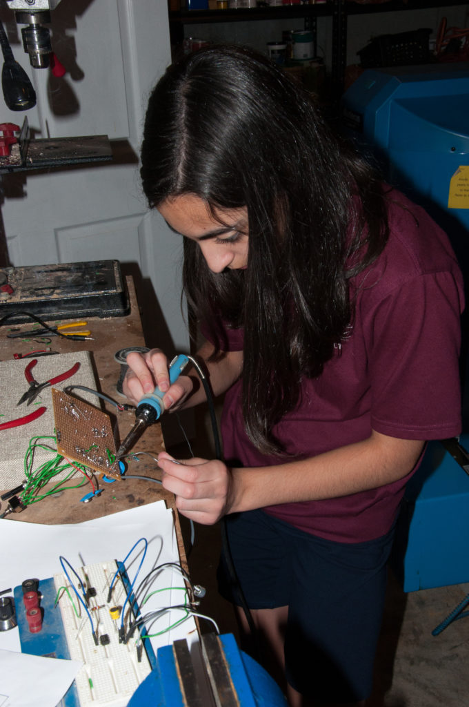 Payton soldering the inner workings of her invention.