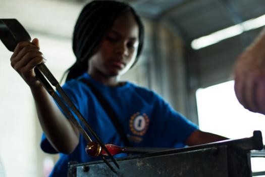 Student of SAFE Alternative program shaping a molten hot piece of glass