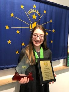 Photo of Isabella Budak holding awards.