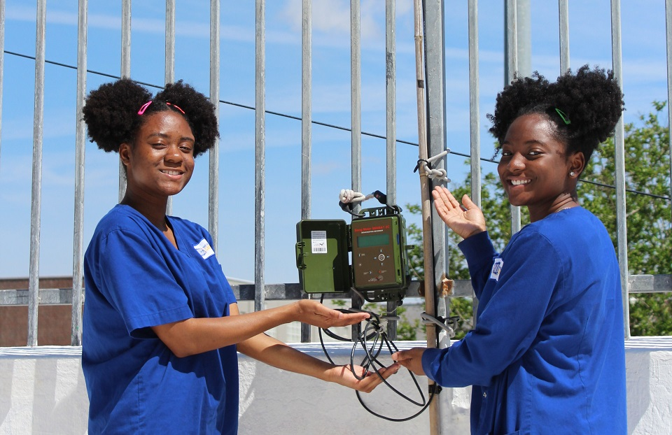 Two of Samuel's students with bat monitoring equipment on their school's roof.