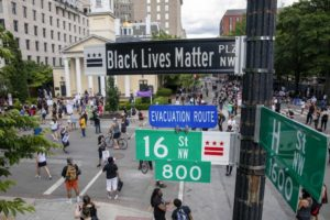 People walk down 16th Street after volunteers, with permission from the city, painted 'Black Lives Matter' on the street near the White House on June 5, 2020, in Washington, D.C. After seven days of protests in D.C. over the death of George Floyd, D.C. Mayor Muriel Bowser has renamed that section of 16th Street 'Black Lives Matter Plaza.'