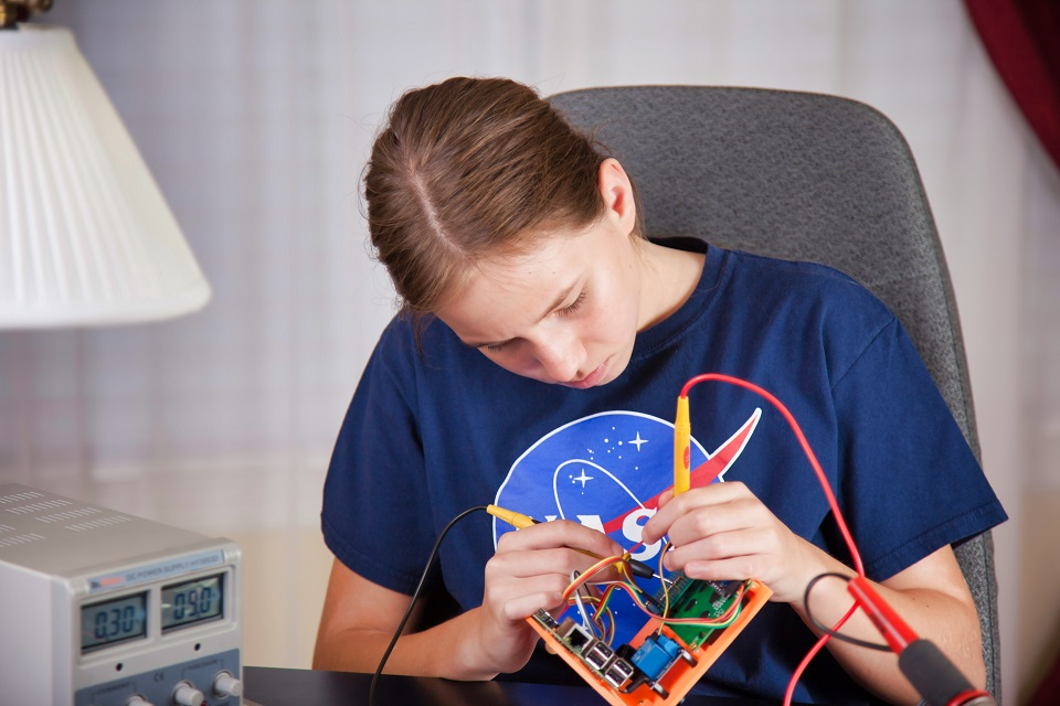 student in blue NASA tshirt working with wires for a project