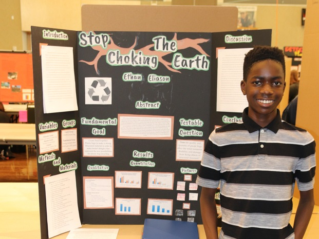 student standing in front of project board