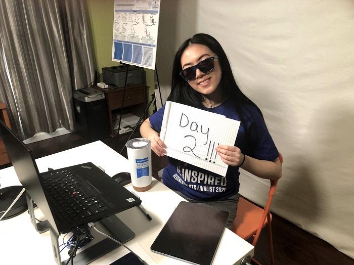 """Regeneron STS 2021 finalist Vivian Yee with """"Day 2"""" sign"""